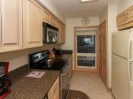 Fully-equipped kitchen in 311 Shorewood in a laundry closet with washer & dryer